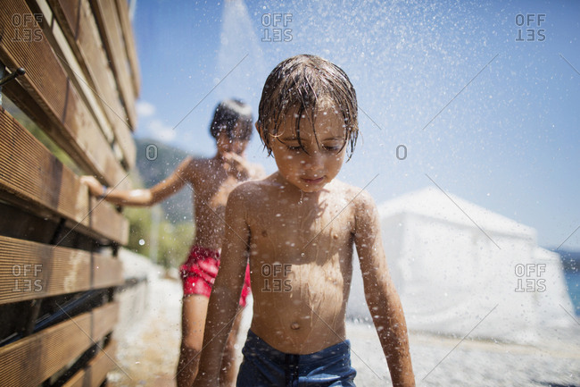 Portait of little boy having shower on the beach