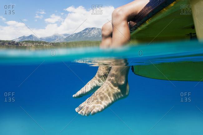 Feet of a boy sitting on boat dangling in water