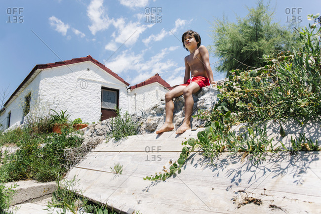 Boy sitting in swimming trunks in sunshine in front of a house