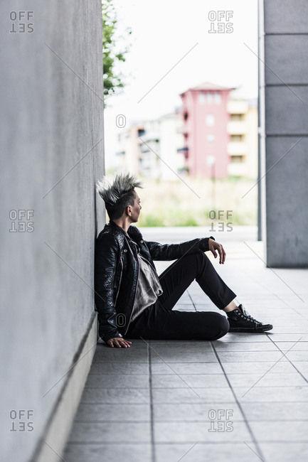Punk woman sitting at a wall