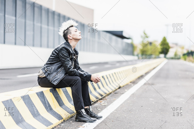Punk woman sitting at the roadside with closed eyes