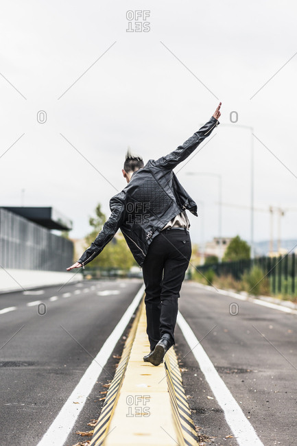 Rear view of punk woman balancing on a barrier at the roadside with outstretched arms