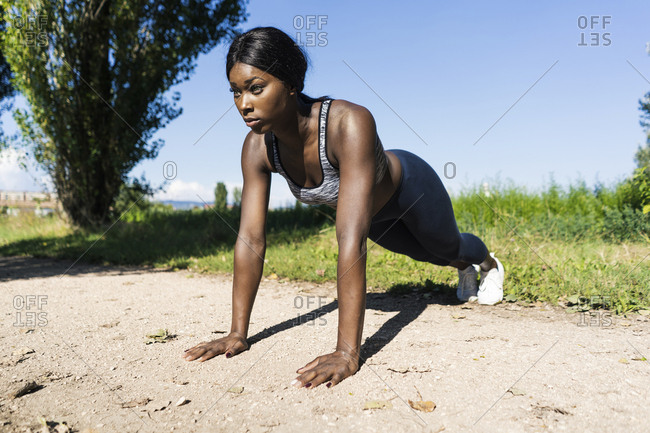 Young athlete doing push ups on the dirt track