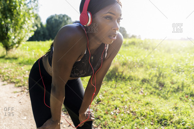 Young athlete in nature- listening music with headphones- preparing for training