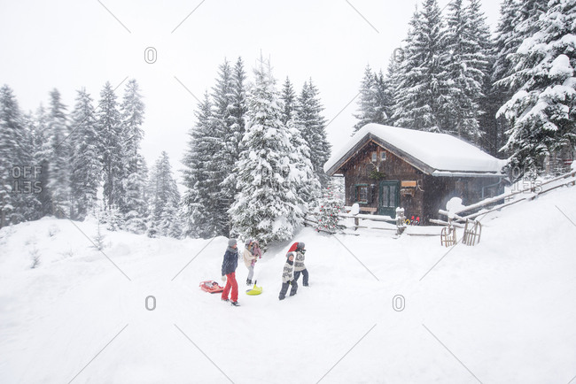 Austria- Altenmarkt-Zauchensee- family with sledges at wooden house at Christmas time