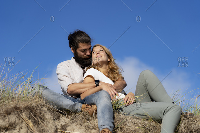 Young couple sitting on a dune in summer- relaxing