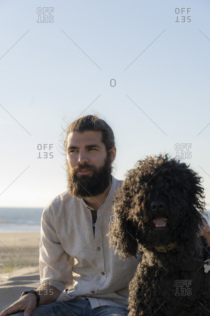 Young man sitting in the dunes with his dog