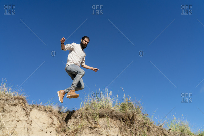 Young man jumping from a sand dune