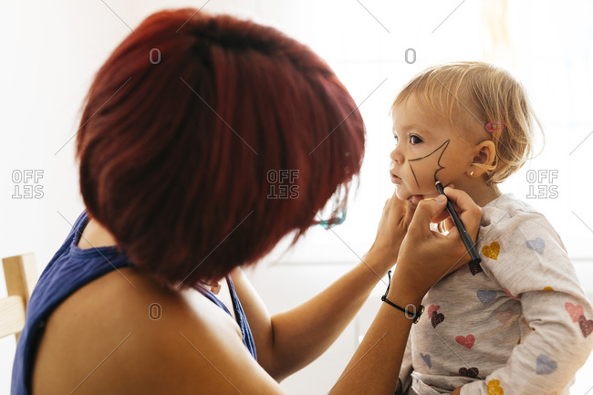 Mother painting her daughter's face for Halloween