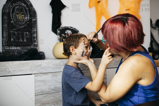 Mother painting her son's face for Halloween