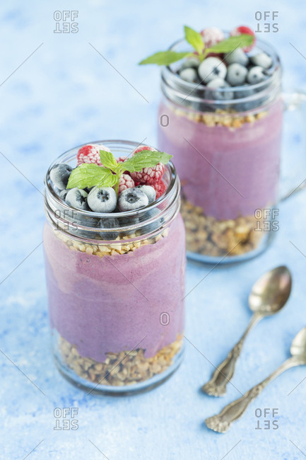 Two glasses of yoghurt with peanut granola- aronia powder and topping of chopped hazelnuts and frozen berries