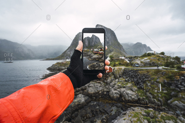 Norway- Lofoten- man's hand taking cell phone picture at the coast