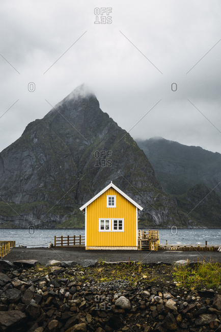 Norway- Lofoten- remote yellow house at rocky coast