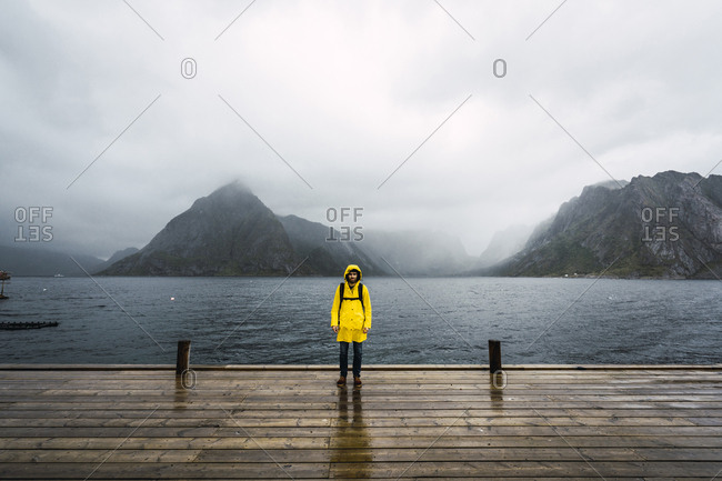 Norway- Lofoten- man standing on a pier at the coast