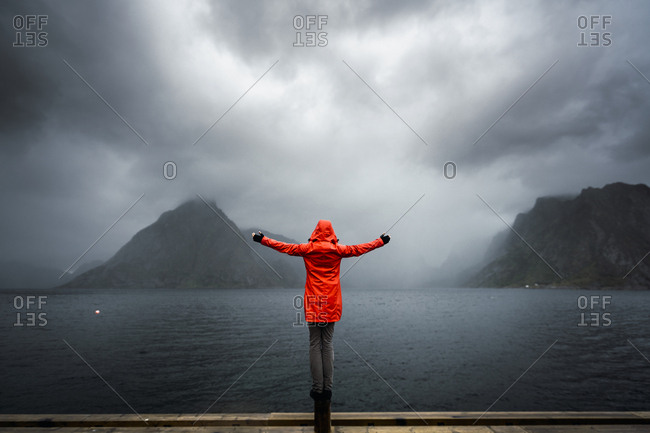Norway- Lofoten- rear view of man balancing on a pole at the coast