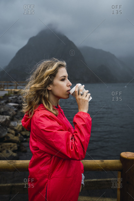Norway- Lofoten- young woman at the coast drinking from takeaway coffee