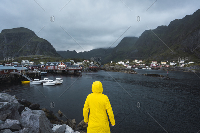 Norway- Lofoten- rear view of man standing in a fishing village at the coast