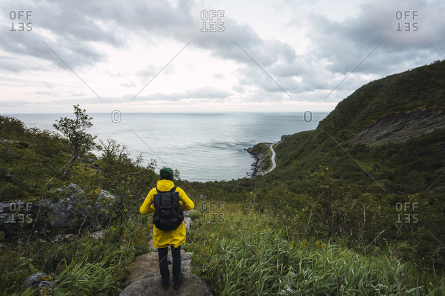 Norway- Lofoten- rear view of man standing on coastal path