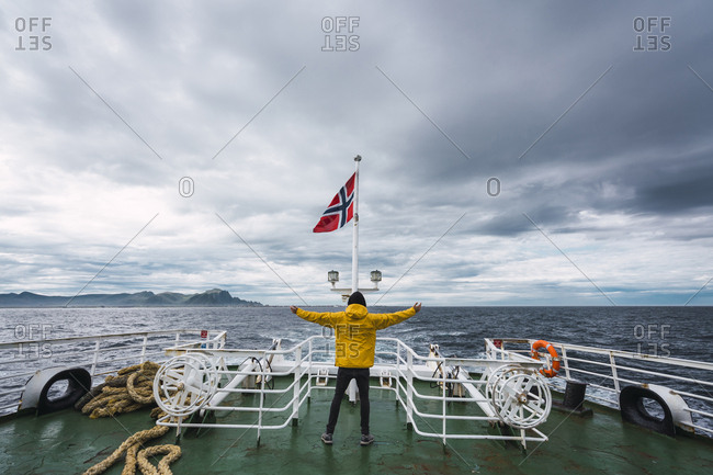 Norway- Senja island- rear view of man standing on ship deck with outstretched arms