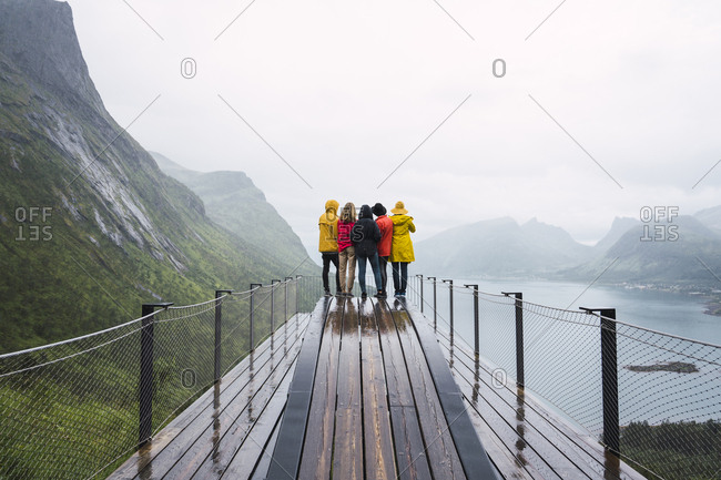 Norway- Senja island- rear view of friends standing on an observation deck at the coast