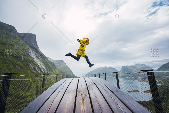 Norway- Senja island- man jumping on an observation deck at the coast