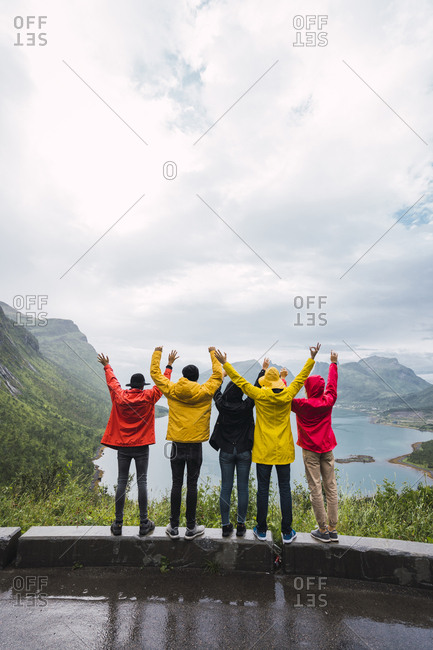 Norway- Senja island- rear view of cheering friends standing on an observation point at the coast
