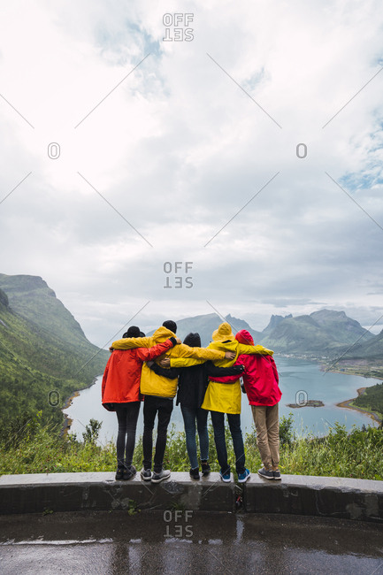 Norway- Senja island- rear view of friends embracing on an observation point at the coast
