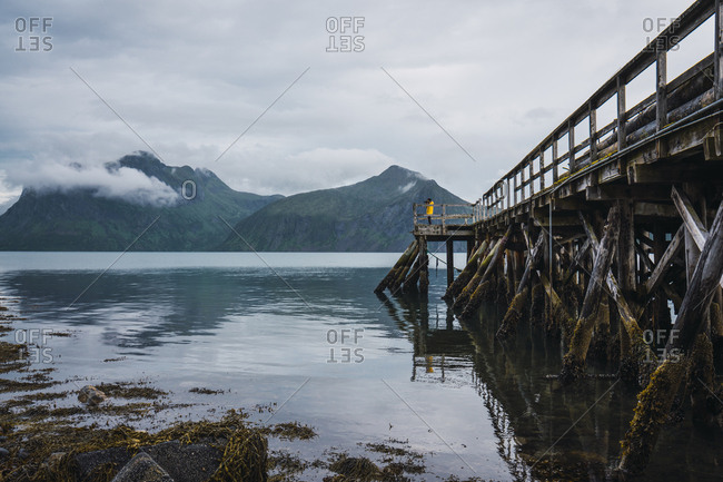 Norway- Senja island- man standing on a jetty at the coast