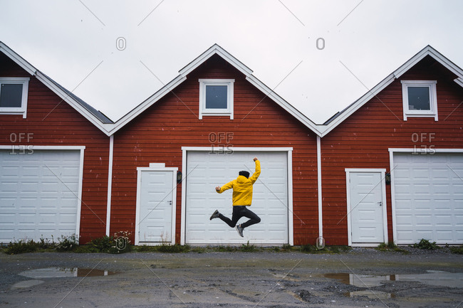 Norway- man jumping in front of row of huts