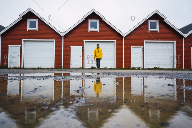 Norway- man standing in front of row of huts