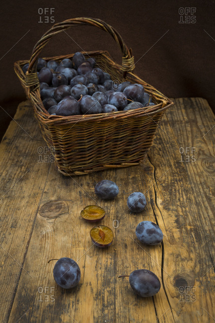 Wicker basket of organic plums- wooden table