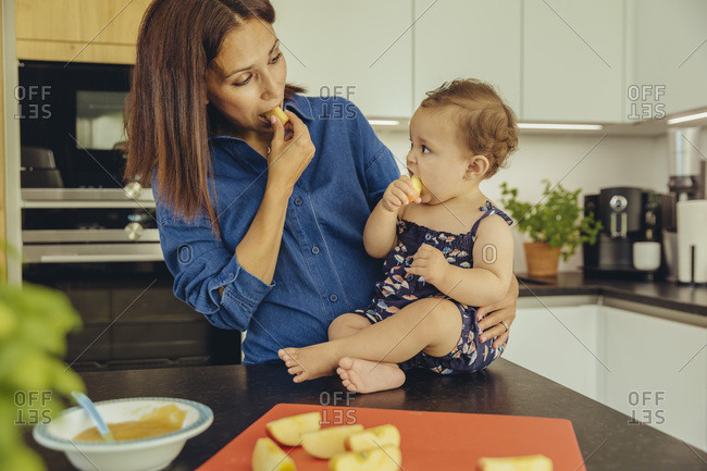 Mother and baby daughter eating apple chunks in kitchen together