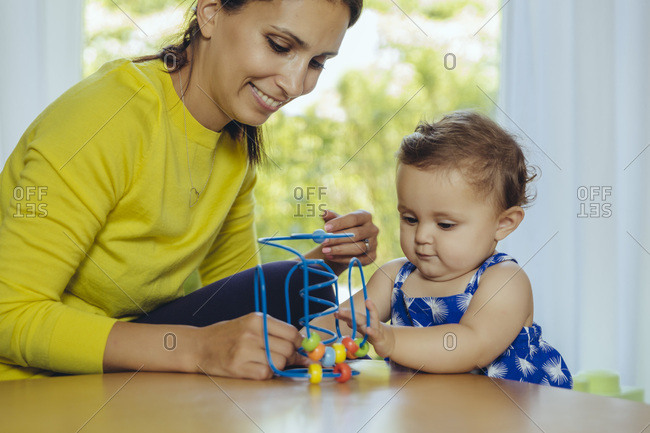 Happy mother and baby daughter playing with motoric loop