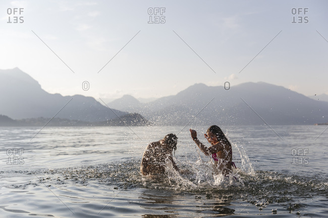 Happy young couple playing in a lake