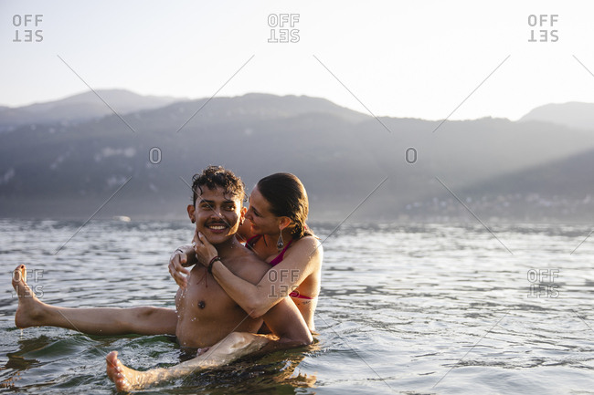 Happy playful young couple in a lake