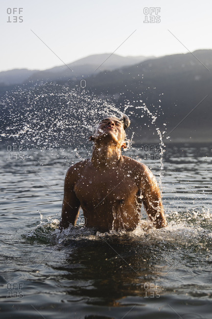 Young man tossing his hair in a lake