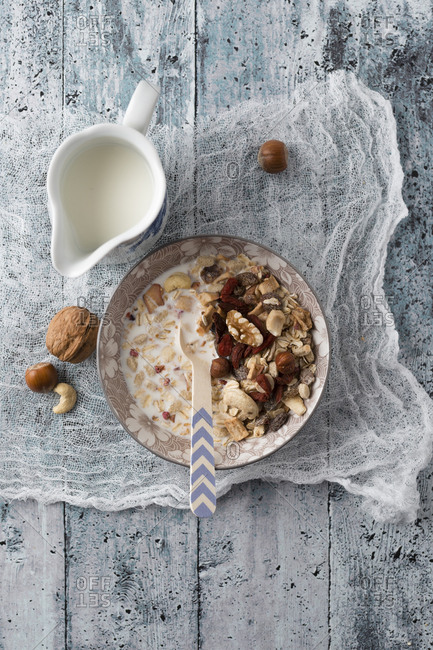 Bowl of granola with nuts and a jug of milk