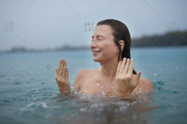 Portrait of young woman bathing in lake on rainy day