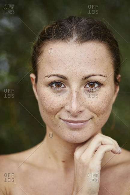 Portrait of freckled young woman in nature