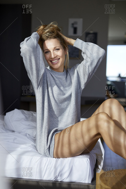 Portrait of smiling blond woman sitting on bed in the morning