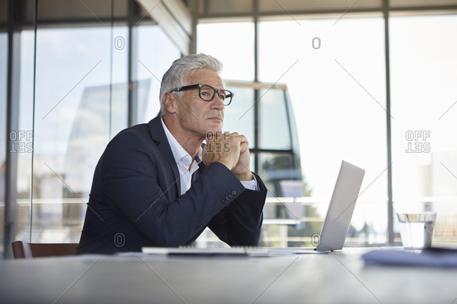 Businessman sitting in office- thinking