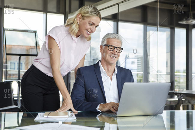 Businessman and woman discussing project in office