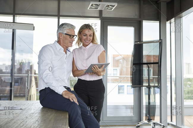 Businessman and woman standing in office- discussing project- looking at digital tablet