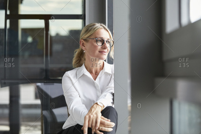 Serene businesswoman sitting on ground- looking out of window