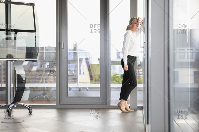 Successful businesswoman standing in office- looking out of window