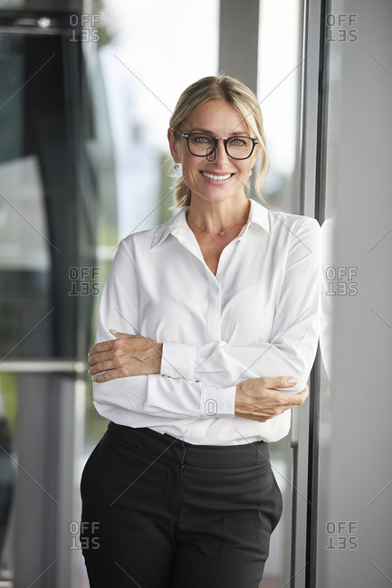 Businesswoman in office leaning against window- with arms crossed
