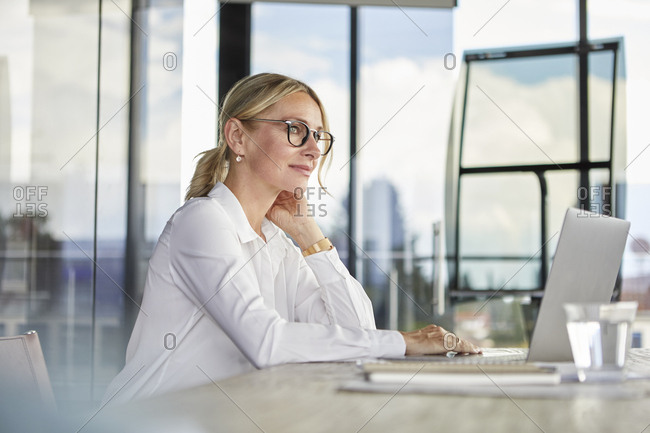 Businesswoman sitting at desk- thinking