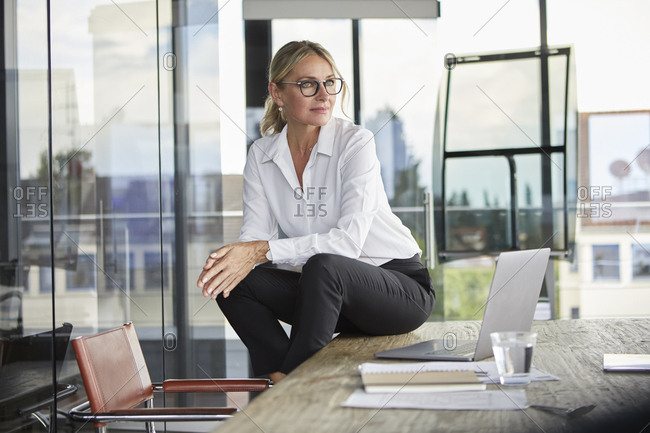 Successful businesswoman sitting on desk- contemplating
