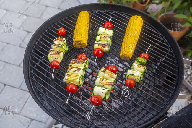 Grilled vegetarian grill skewers- tomato- sheep cheese and zucchini slices- corn cobs on grill