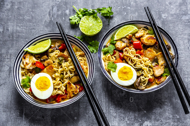 Ramen soup with egg- noodles- chicken meat- paprika- mushroom- spring onion- lime and coriander